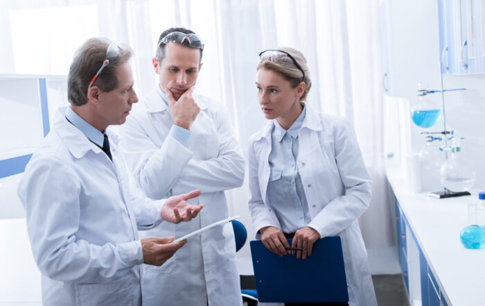Concentrated colleagues in white coats standing and talking in chemical lab