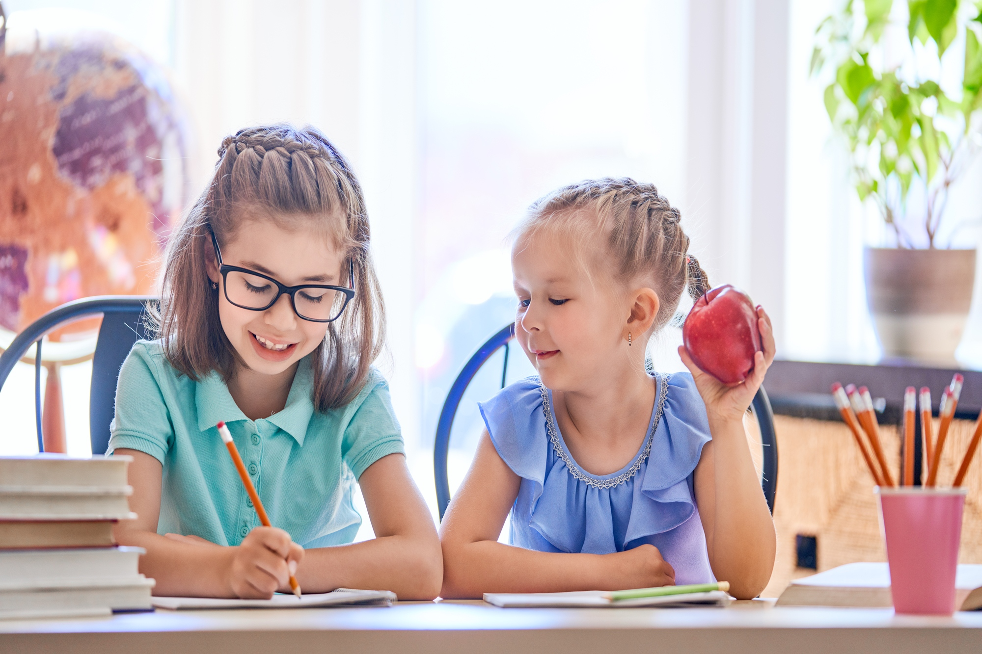 Back to school! Happy cute industrious children are sitting at a desk indoors. Kids are learning in class.
