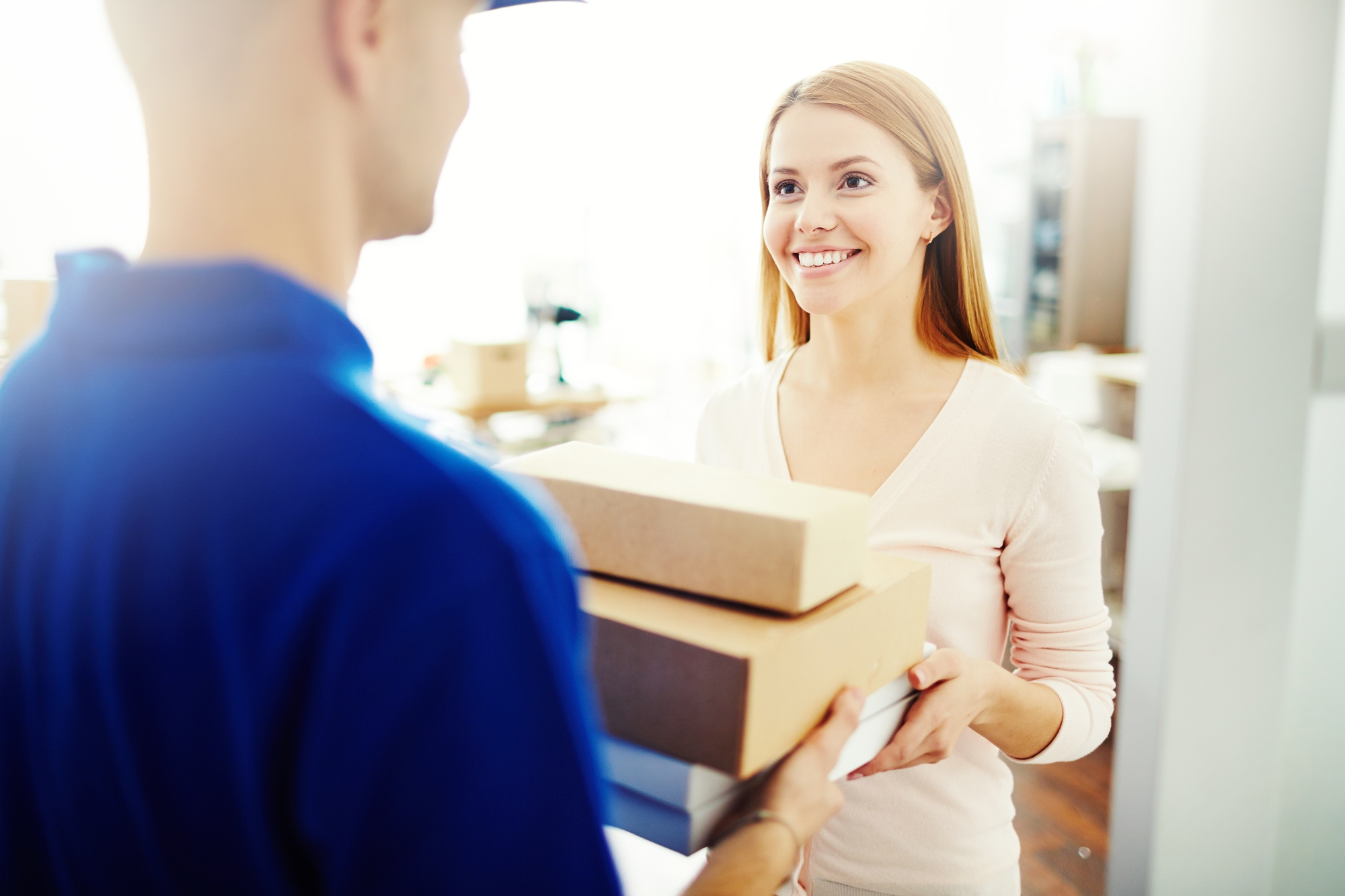 Happy young woman receiving a box from mailman