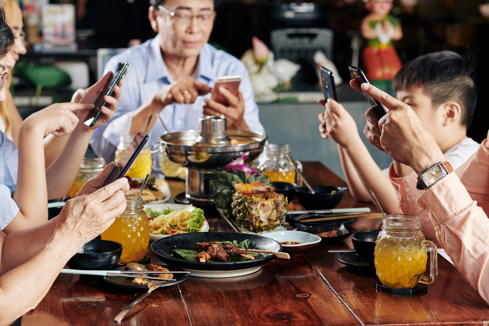 Family members with smartphones spending time on social media instead of talking during family dinner