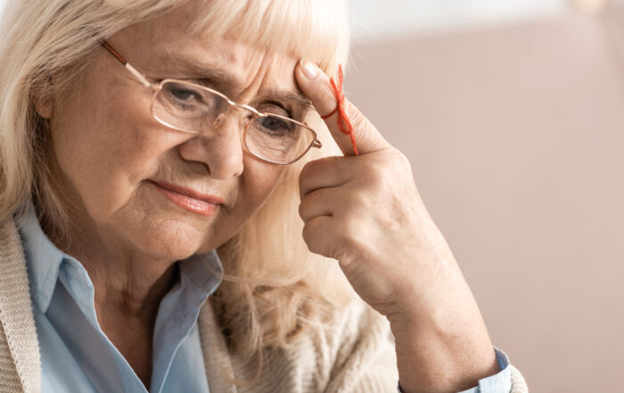 pensive senior woman with alzheimers disease string human finger reminder
