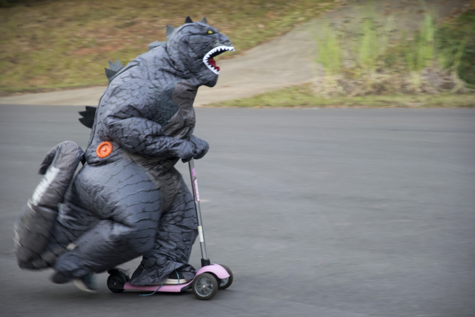 child in an inflatable godzilla costume on a scooter