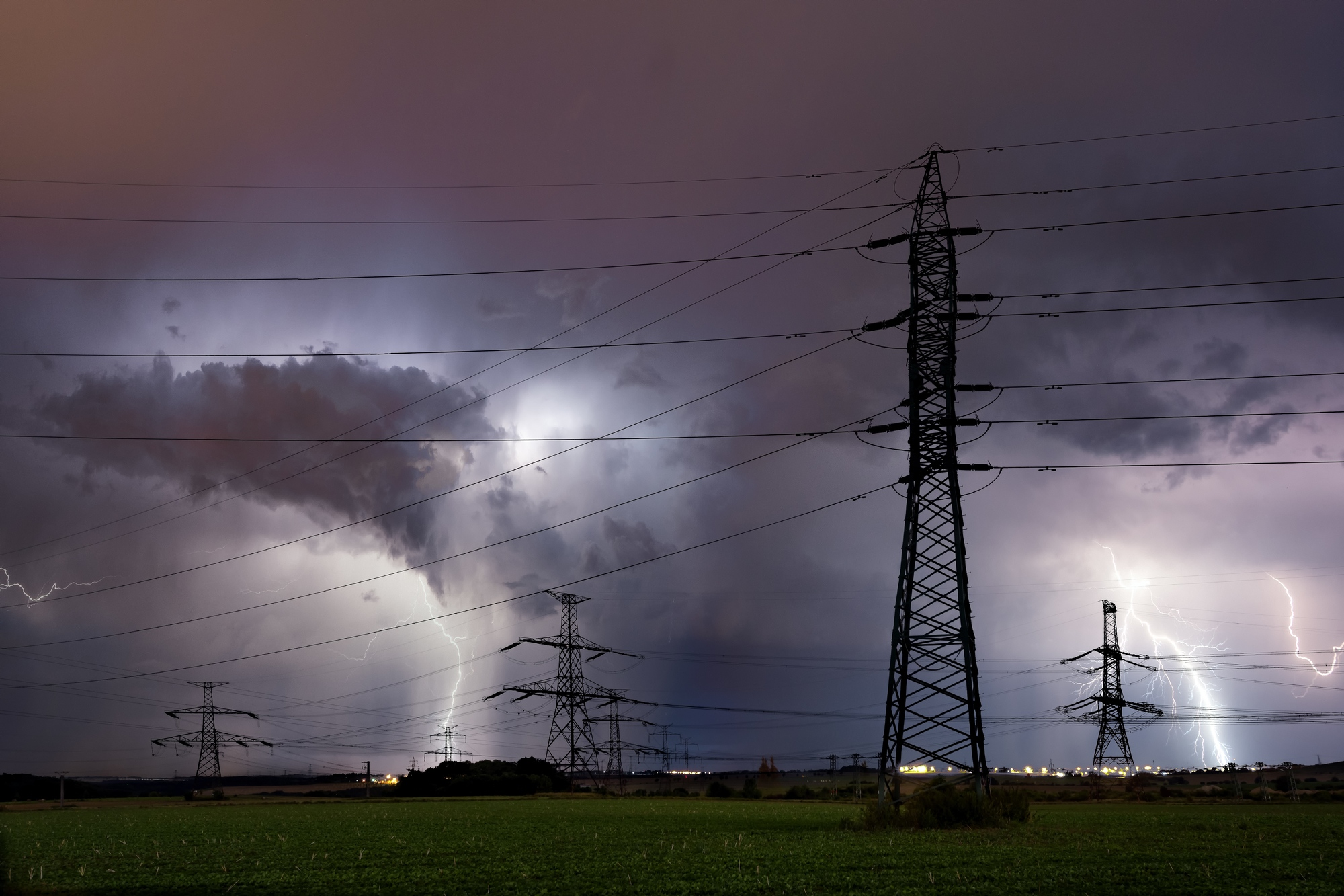 Silhouette of high voltage electrical mast with lightning storm over Prague, Czech republic